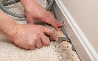 Handy Man Installing Carpet - Flooring Installation